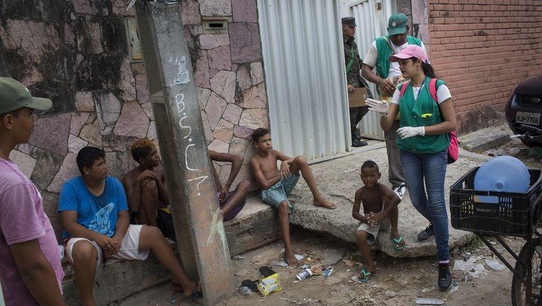 Erica Silmara (28), voorzitter van de antimuggencampagne in Olinda, praat met jongeren in een sloppenwijk. 'Een mug heeft weinig water nodig om zich voort te planten.' Beeld Rafael Fabres