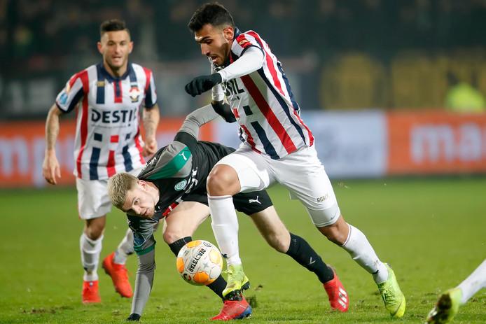 Willem II-spits Evangelos Pavlidis snelt voorbij Django Warmerdam van FC Groningen. Op de achtergrond kijkt Pol Llonch toe.