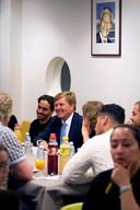 Koning Willem-Alexander luistert naar verhalen tijdens de  iftar-ontmoeting in buurthuis Mandelaplein.