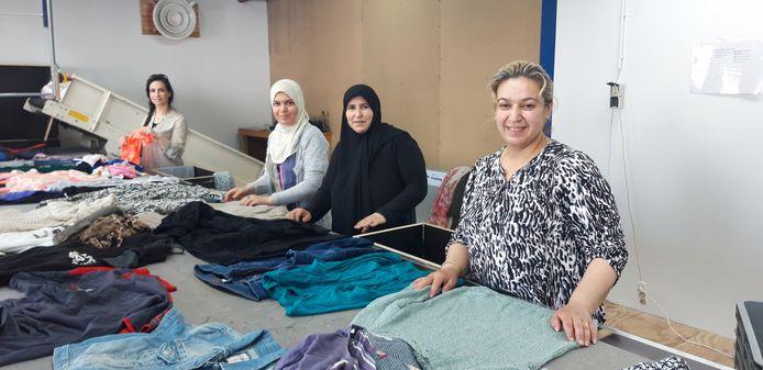 Almelose statushouders aan de slag bij de textielsortering in De Beurs in Tubbergen, waar door de coronacrisis een stuk minder mensen aan het werk zijn.