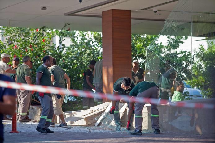 Werklieden ruimen het gebroken glas en puin op bij de ingang van het hotel.