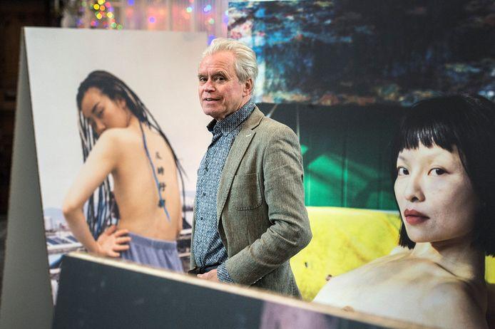 Curator Geert van Eyck neemt afscheid van BredaPhoto. Hij poseert in de grote kerk tussen het werk van Luo Yang uit China, als onderdeel van de China Imagined Expositie.