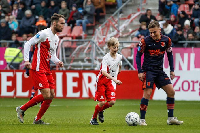 Onder toeziend oog van FC Utrecht-speler Sander van der Streek (L) mag de 11-jarige Wikke richting doel van RKC om te scoren. Wikke is slechtziend en heeft nog maar zeer beperkt zicht.