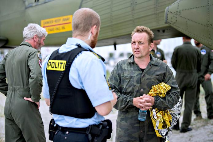 Madsen praat met een politieagent na zijn redding uit de gezonken onderzeëer.