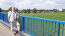 Harrie Bakker op de A50-brug, met op de achtergrond de Maas en de veevoerfabriek van De Heus in Ravenstein.