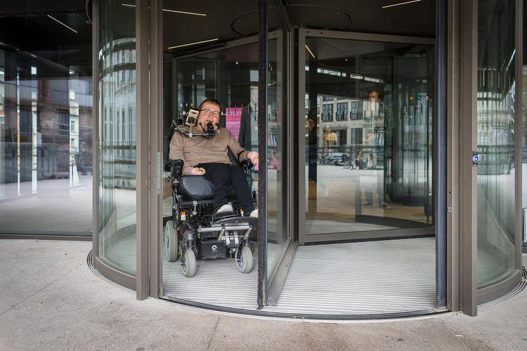 Eddy Herrebout kan maar net met zijn rolstoel in de draaideur.