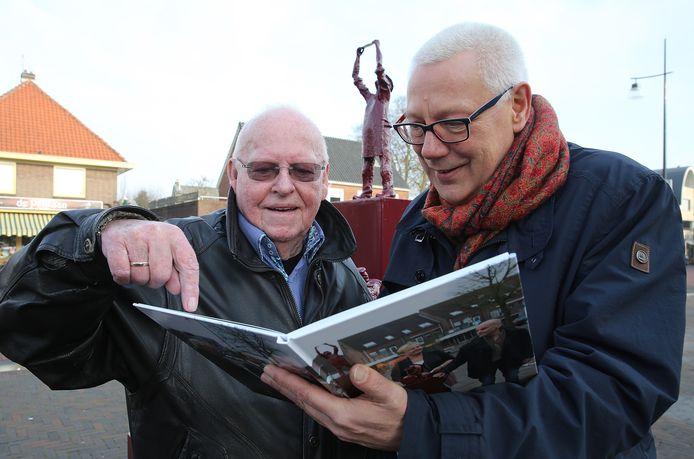 Wethoud Eef van Ooijen (rechts) neemt een boek over het ontstaan van het Papierscheppersmonument in ontvangst van Bruno de Vries.