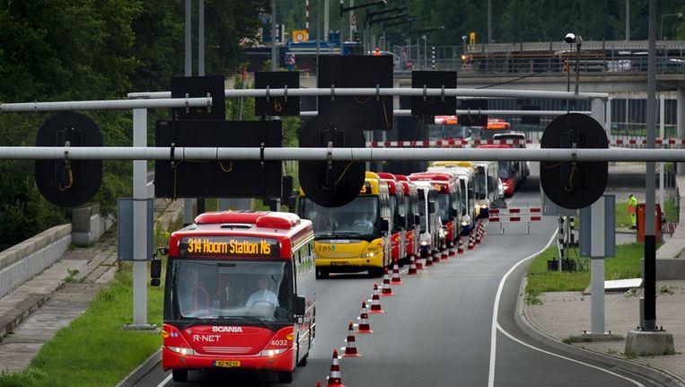 Een lange file van bussen voor de IJtunnel vanmorgen. Sommige bussen reden naar de pont en zetten hun passagiers daar af. Beeld Klaas Fopma