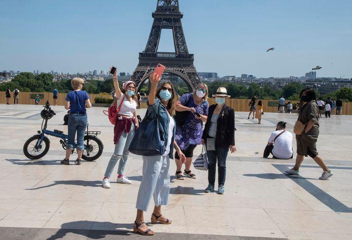 Toeristen met een mondkapje maken een selfie met de Eiffeltoren