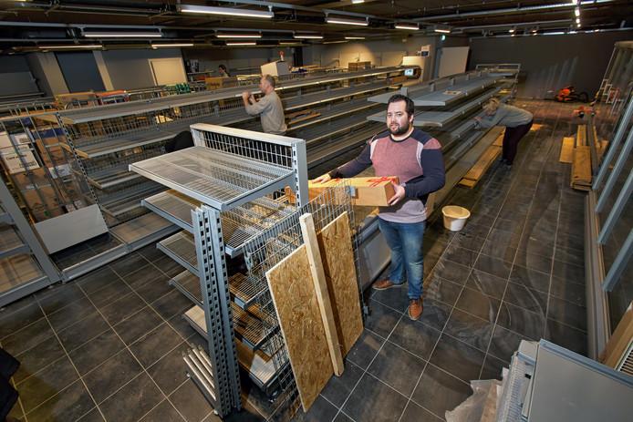 Bedrijfsleider Martijn van Bijsterveld (voorgrond) is druk in de weer met de inrichting van de buurtsuper.