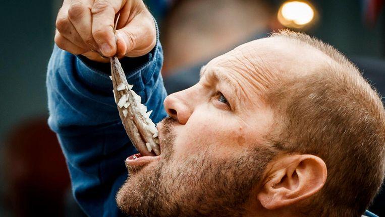 Een man geniet van een haring met uitjes. Beeld anp