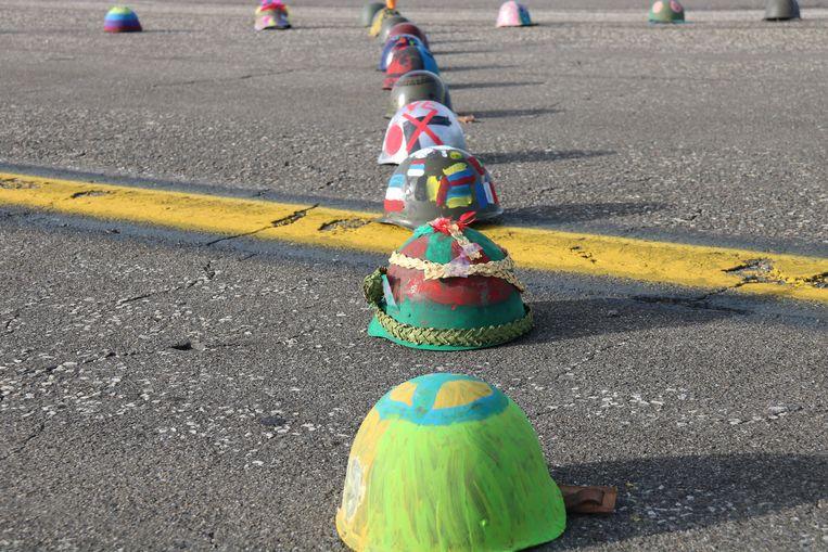 De leerlingen versierden honderd oorlogshelmen met allerlei vredesboodschappen