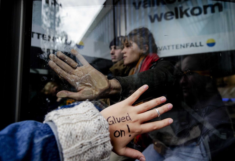 Actievoerders hebben zich bij Vattenfall vastgeplakt aan de toegangsdeur. Beeld EPA/Robin van Lonkhuijsen