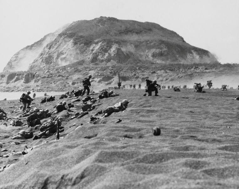 Amerikaanse mariniers na de landing op Iwo Jima op 19 februari 1945. Op de achtergrond is de berg Suribachi te zien.