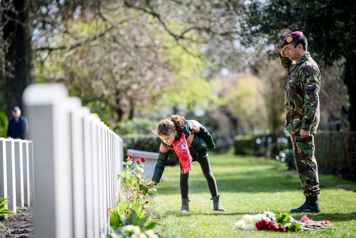 Terwijl zijn dochter Lisa bloemen legt op de graven van Britse soldaten op de Oosterbegraafplaats brengt Micha Peters een groet aan de bevrijders van Enschede.