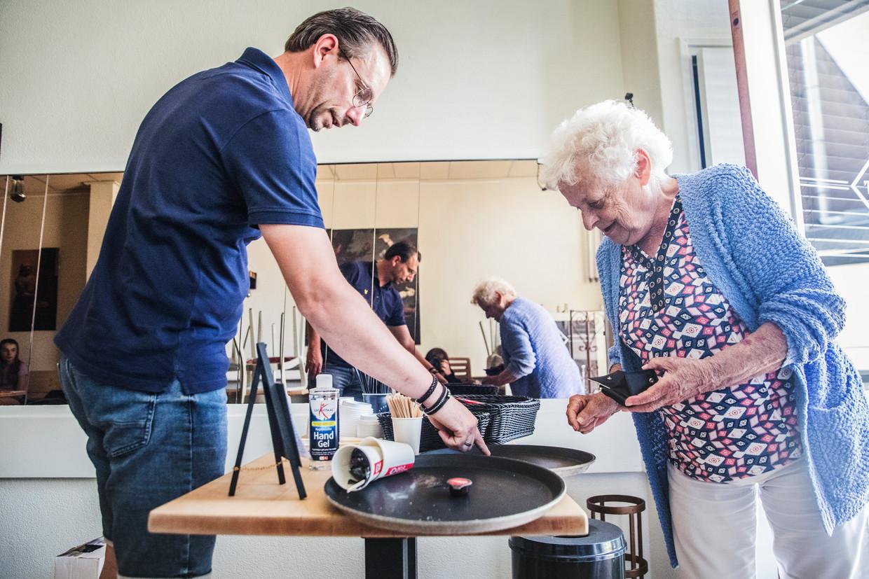 Arthur Lauer rekent bij de ingang van zijn lunchroom een kop koffie af met een klant.  Beeld Aurélie Geurts