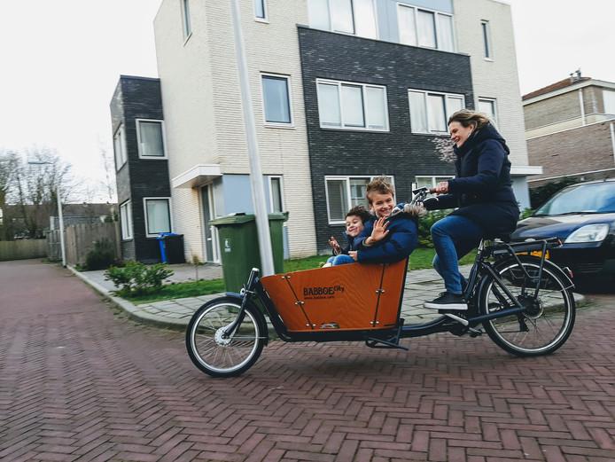 """Lilian Vis sjeest met Max en Tim op haar elektrische bakfiets door de straat. ,,In het begin was het wel een beetje wennen."""""""
