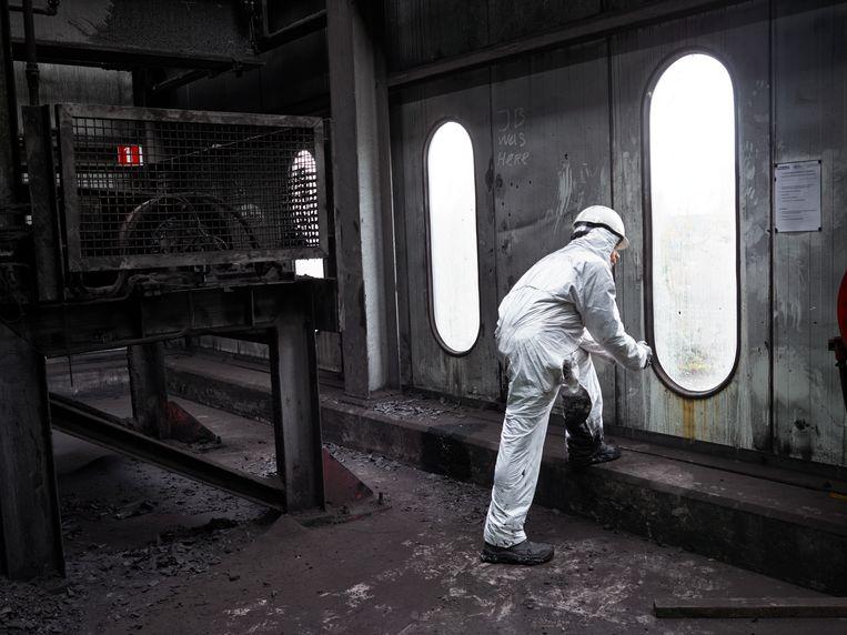 Een lid van de industriële schoonmaakploeg neemt even pauze tijdens het schoonmaken van de kolentransportband die van het Amsterdamse Overslagbedrijf  (OBA) naar de Hemwegcentrale loopt. Beeld Henk Wildschut