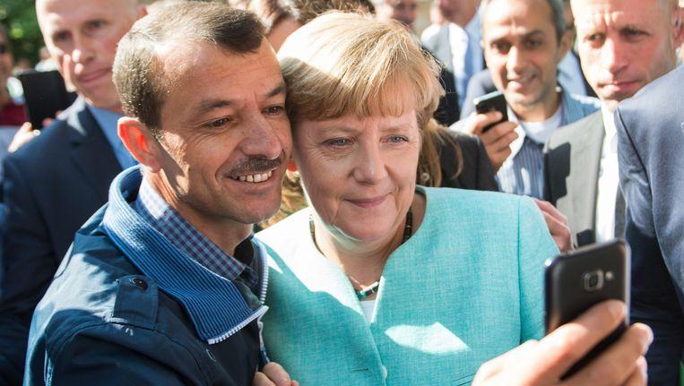 Merkel poseert voor een selfie in een accommodatie voor vluchtelingen in Berlijn