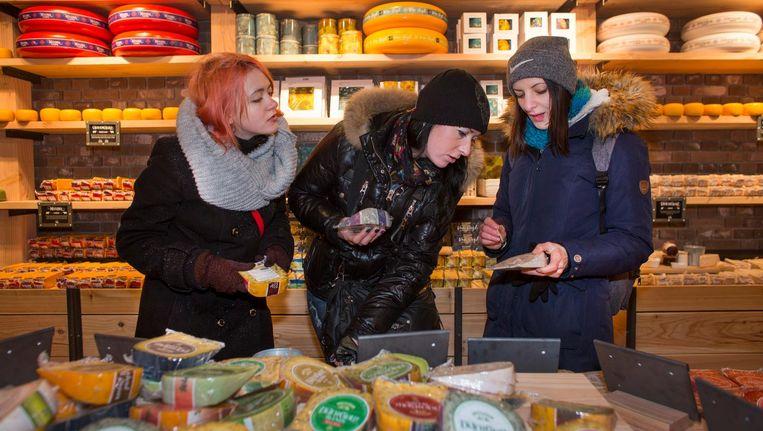 Toeristen in de Cheese Company op het Damrak in Amsterdam. Beeld null