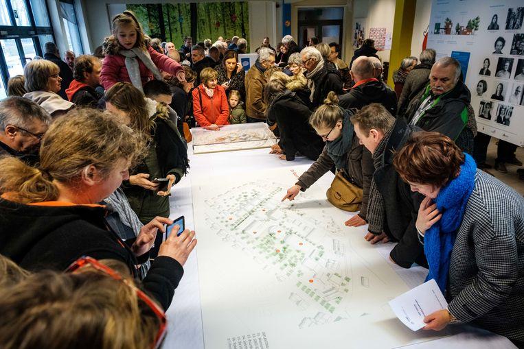 Buurtbewoners bekijken de plannen voor het schoolproject.