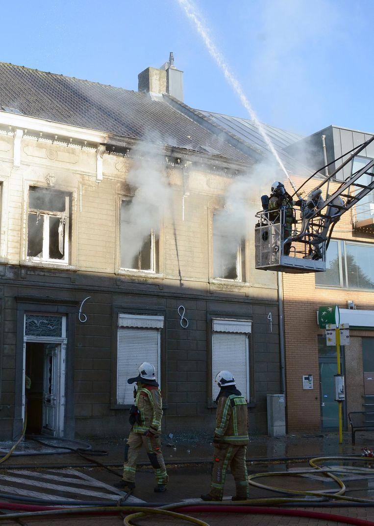 De brandweer bij het gebouw waaruit rook ontsnapt.