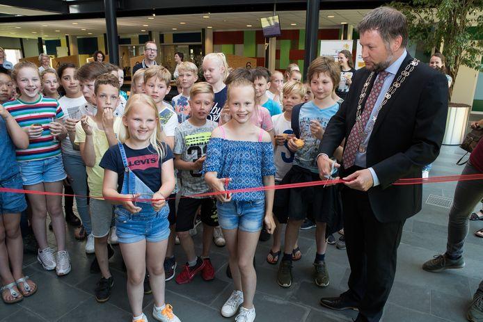 Linde Reimert (links) en Cailyn Dekker van de basisschool de Linderte openen met burgemeester Martijn Dadema de expositie in het Raalter gemeentehuis.