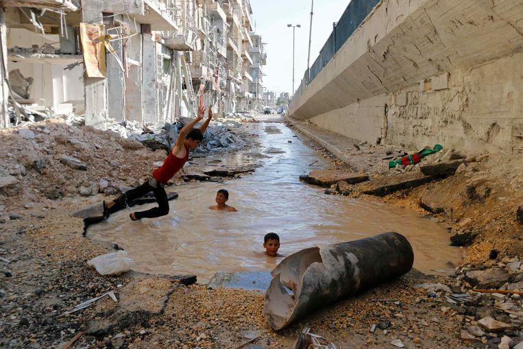 Kinderen in Aleppo duiken in een krater die volgens activisten het gevolg is van de ontploffing van een vatenbom.