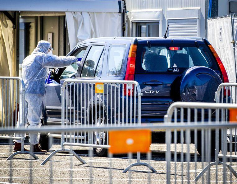 In Goirle is een drive-in huisartsenpost geopend waar patiënten met het coronavirus vanuit hun auto geholpen worden. Beeld EPA