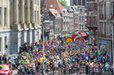 Het peloton kruipt door de massa op de Stadhuisbrug.