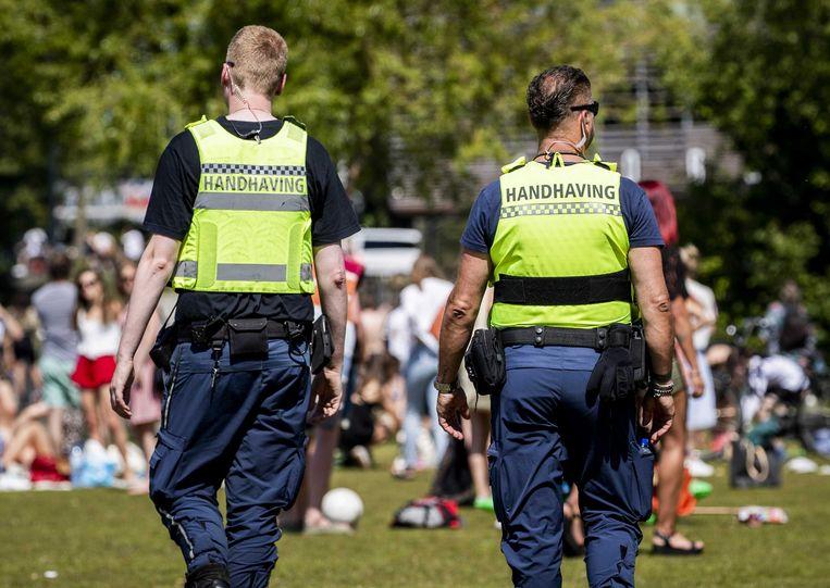 Handhavers en politie ontruimen Park Somerlust vanwege de te grote drukte. Beeld ANP/Remko de Waal