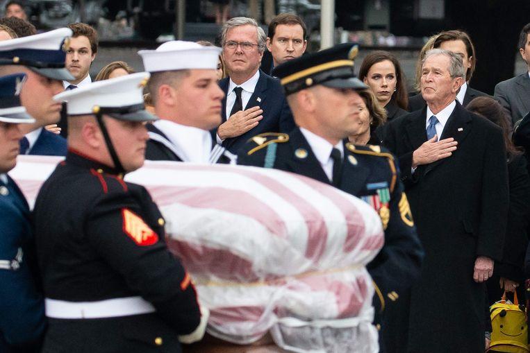 Broers Jebb en George Bush (met de hand op het hart) kijken toe hoe een erewacht de kist van hun vader wegdraagt.