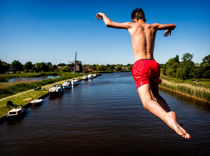 Een jongen springt van een brug in het water tijdens een mooie dag
