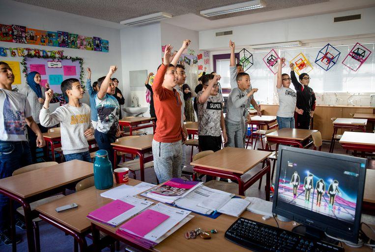 Basisschoolleerlingen uit groep 8 van de Prinses Marijkeschool doen een warming-up voordat zij zich buigen over de Cito eindtoets.  Beeld ANP
