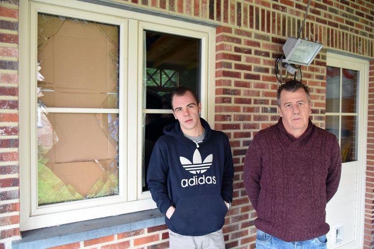 Zoon Jannick en Dominique Wouters bij het kapotte raam langs waar de inbrekers binnendrongen.