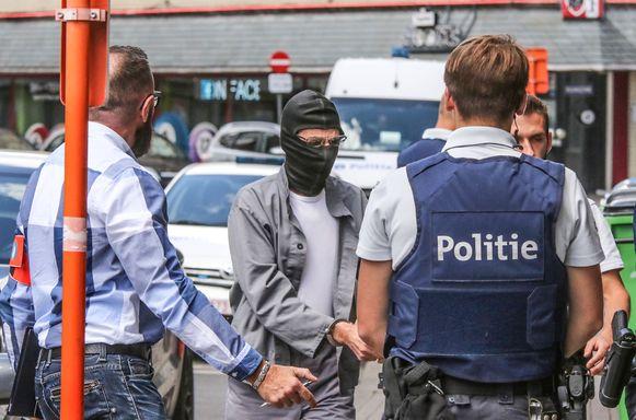 Reconstructie van de moord op de 56-jarige Alia Belromari, met beschuldigde Luc Vanden Bussche die door de politie het appartement wordt binnengeleid