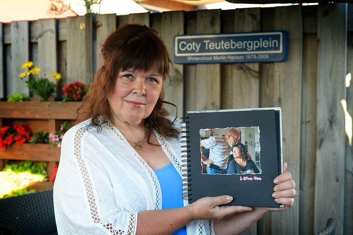 Antoinette Rosbergen-Teuteberg met een foto van haar vader Coty op het naar hem vernoemde pleintje in haar tuin.