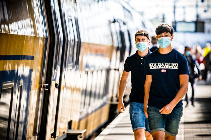 Reizigers met mondkapjes op het Centraal Station van Eindhoven.
