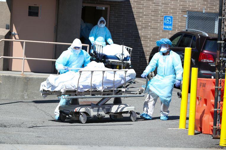 Medewerkers in de gezondheidszorg brengen lichamen van overledenen naar tijdelijke mortuaria in containers bij het Wyckoff Heights Medical Center in Brooklyn, New York.   Beeld Anadolu Agency via Getty Images