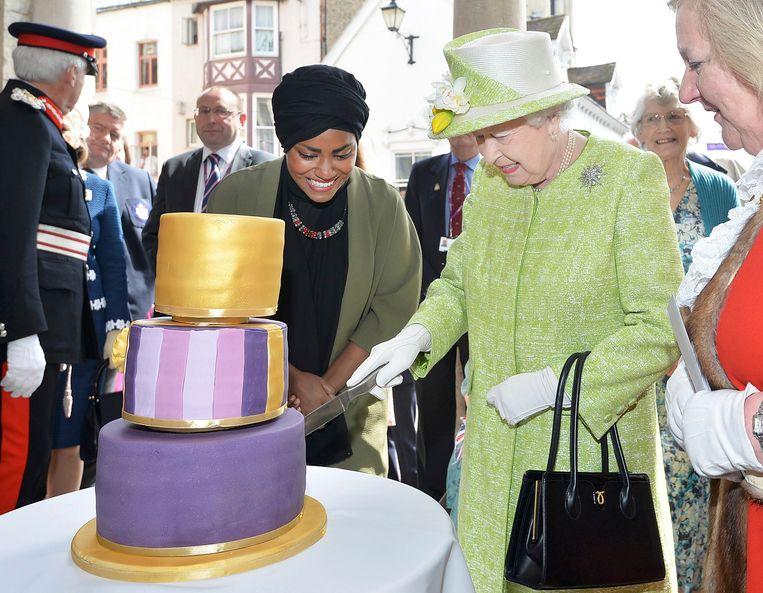 Queen Elizabeth snijdt de taart van Nadiya Hussain. Beeld reuters