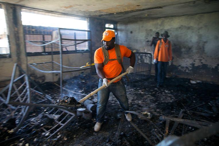 Medewerkers van de civiele bescherming ruimen puin van het afgebrande ziekenhuis.