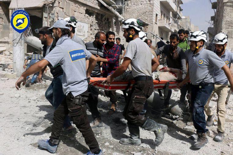 Hulpmedewerkers van de White Helmets dragen een gewonde man weg in de wijk al-Sakhour, in het oosten van Aleppo. Beeld ap