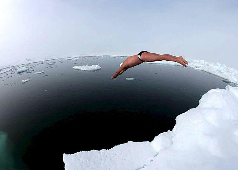 De Britse duurzwemmer Lewis Gordon Pugh duikt van een ijsschots op de Noordpool. Beeld EPA