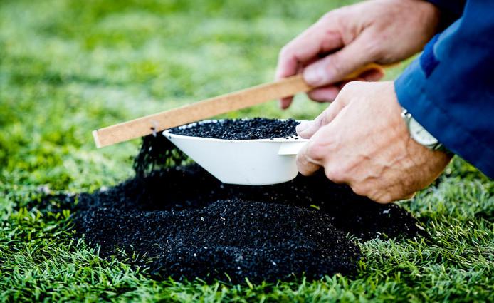 Een medewerker van Vereniging Band en Milieu verzamelt rubberkorrels op een voetbalveld van kunstgras van voetbalvereniging Roda 23.  ANP KOEN VAN WEEL