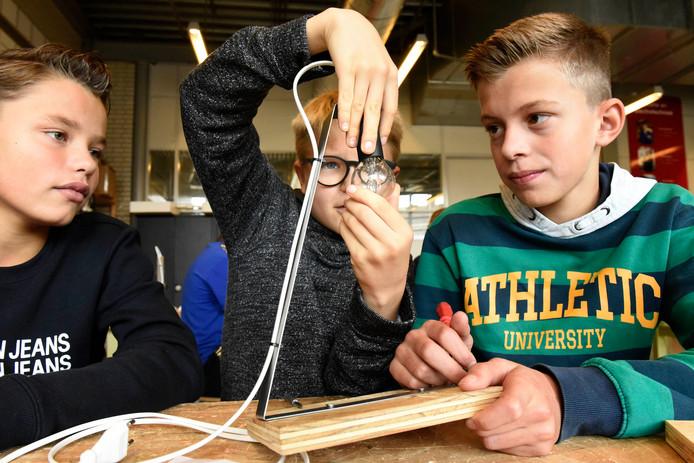 Leerlingen Cas, Simon en Freek maken een leeslampje tijdens de Leesplezierdag op het Kalsbeek College locatie Bredius.