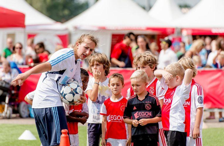 Jonge fans volgen een voetbalclinic tijdens de open dag van Ajax. Beeld anp