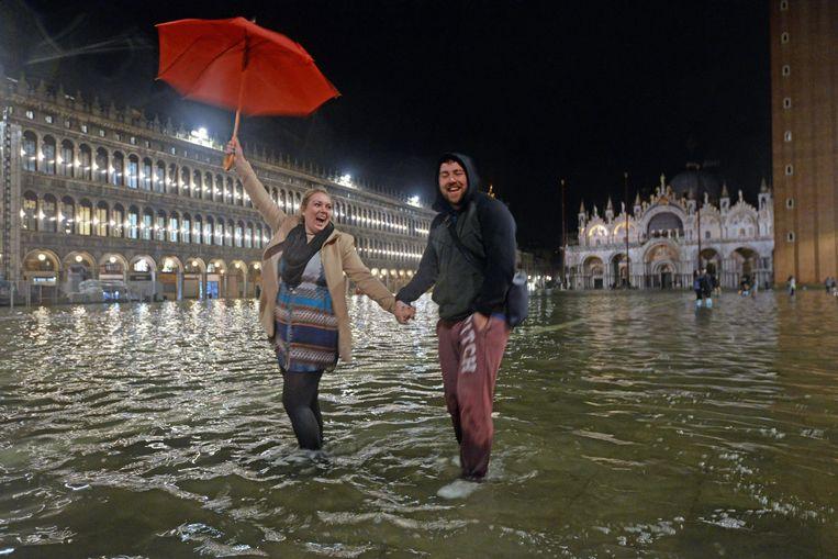 Jonge toeristen bij hoog water op San Marco-plein in Venetië.  Beeld EPA