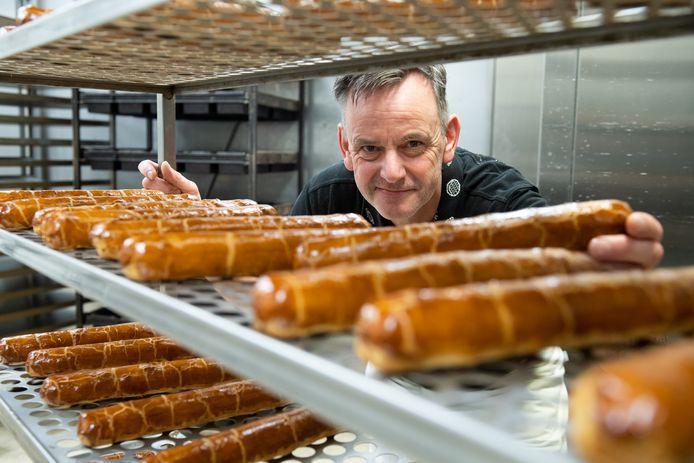 Bakker Theo Pastoor bij de banketstaven die net uit de oven komen.