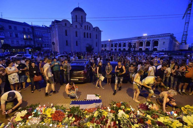 Bij de Nederlandse ambassade in Kiev hangen de vlaggen halfstok en hebben veel mensen bloemen neergelegd. Beeld afp