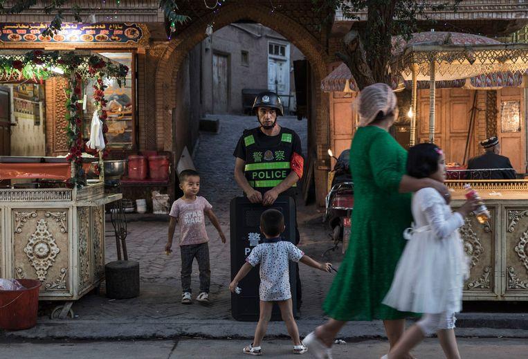 Oeigoerse kindjes in de stad Kashgar plagen een Chinese politieman. Beeld Getty Images